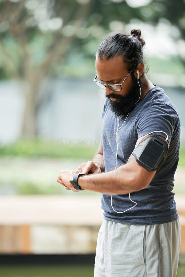 Coureur indien vérifiant le temps photographie stock libre de droits