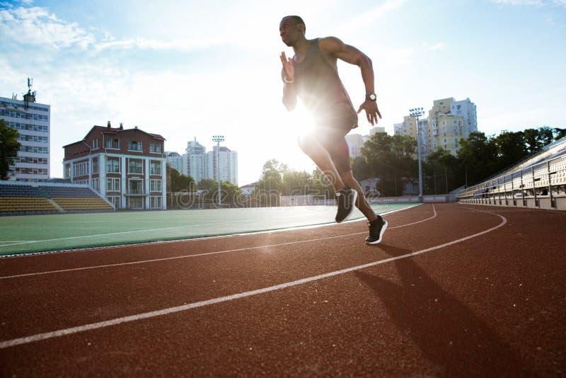 Coureur masculin pratiquant le sien sprint dans le champ de courses de stade d'athlétisme photo libre de droits