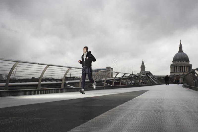 Coureur masculin sur le pont de millénaire avec St Paul derrière image libre de droits
