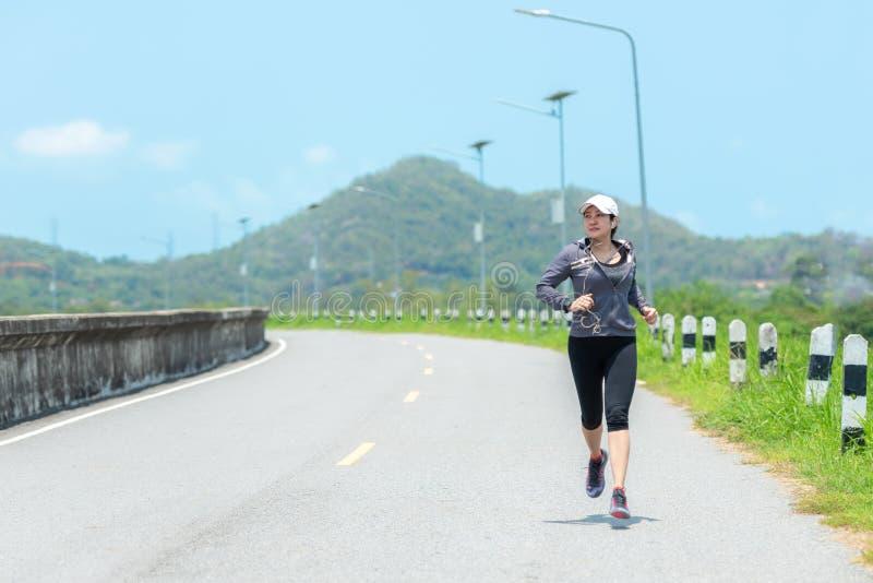 Coureur sportif de femme fonctionnant par la route S?ance d'entra?nement en parc photos libres de droits