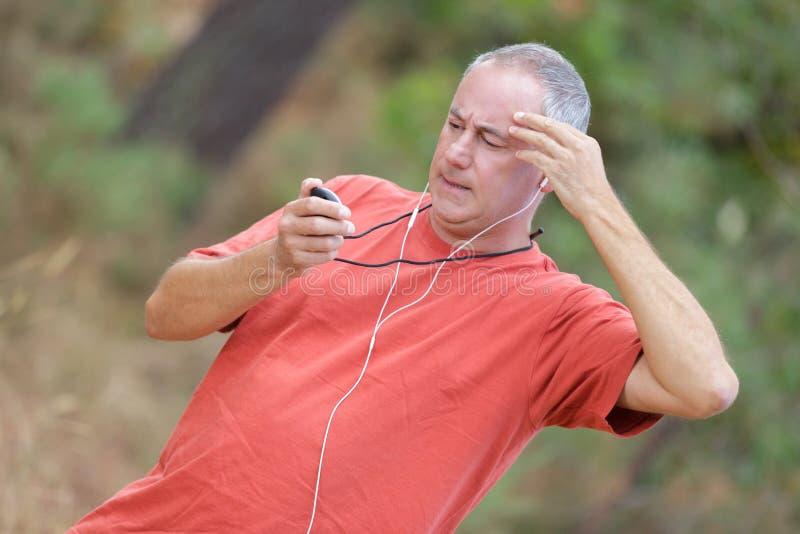 Coureur sur la traînée de forêt de montagne vérifiant regardant le chronomètre images stock