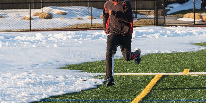 Coureur sur le champ vert de gazon avec la neige là-dessus photos stock