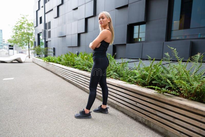 Coureur urbain femelle sûr se tenant avec ses bras croisés photo libre de droits