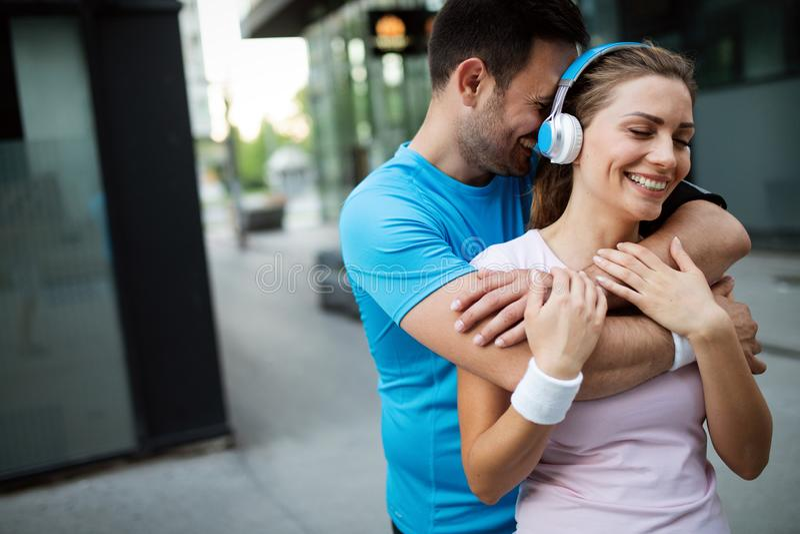 Coureurs convenables épuisés de couples après séance d'entraînement de fonctionnement de forme physique dehors photographie stock