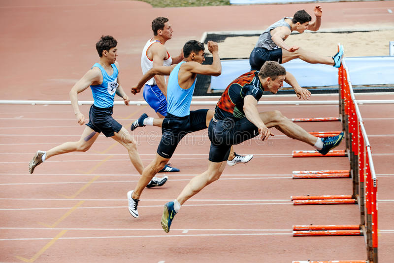 coureurs d'hommes courant la course dans des obstacles de 110 mètres photographie stock