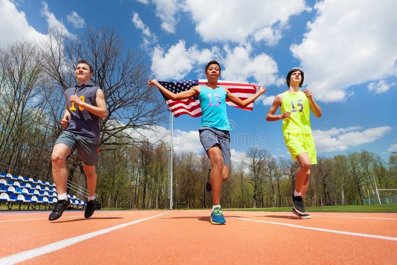 Coureurs de gain avec le drapeau des Etats-Unis célébrant la victoire image libre de droits