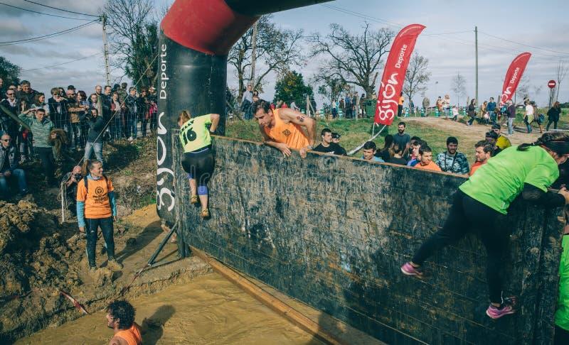 Coureurs escaladant le mur dans un essai de course d'obstacle extrême photographie stock