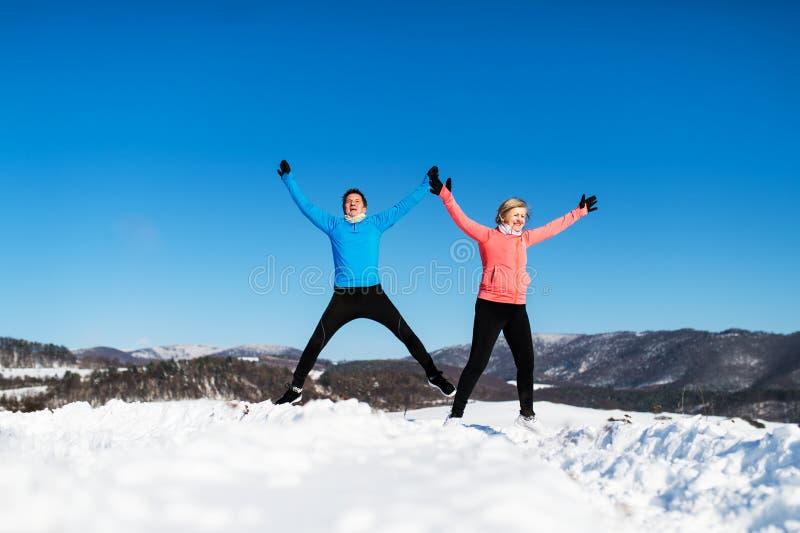 Coureurs supérieurs heureux de couples sautant en nature d'hiver image stock