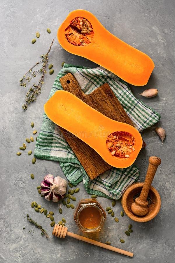 Courge crue de potiron ou de butternut, planche à découper vide, herbes, miel sur un fond gris Vue sup?rieure, configuration plat images stock