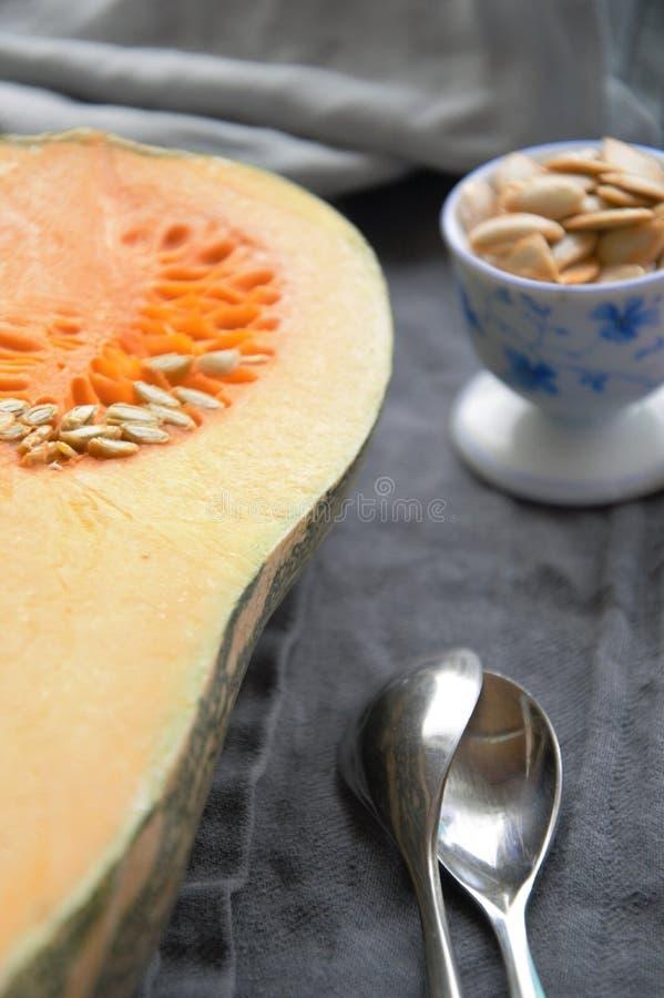 Courge de Butternut coupée en tranches dans la moitié sur une table avec des graines dans une tasse curcubitaceae image libre de droits