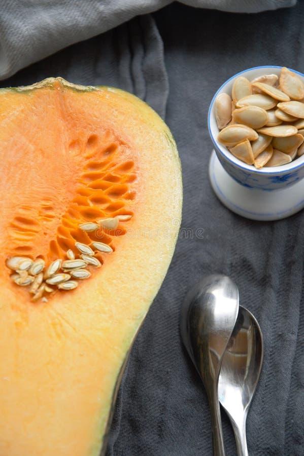 Courge de Butternut coupée en tranches dans la moitié sur une table avec des graines dans une tasse curcubitaceae images stock
