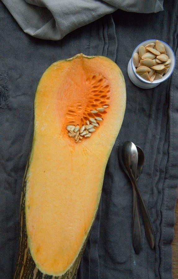 Courge de Butternut coupée en tranches dans la moitié sur une table avec des graines dans une tasse curcubitaceae photographie stock