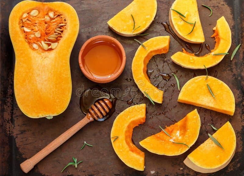 Courge de butternut organique crue coupée en tranches sur une moule avec du miel et le romarin images stock