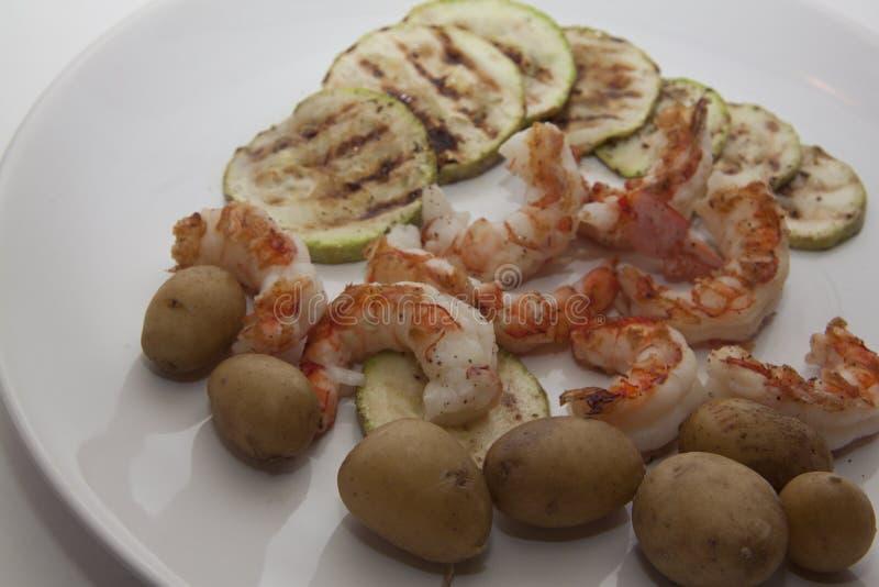 Courgette, aardappel op garnalen stock foto