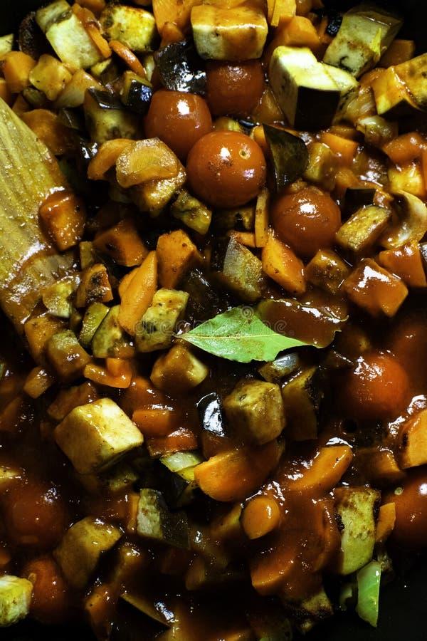 Courgette, aubergine, piment, sauce tomate, feuille de laurier, carotte, tomates, et aneth braisés dans la casserole avec les spa image stock