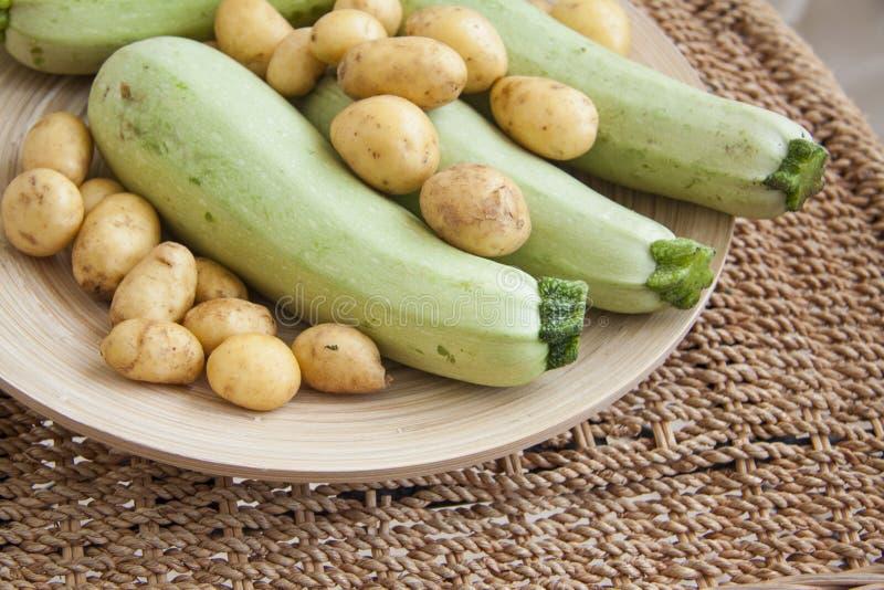 Courgette en aardappel in mand stock fotografie