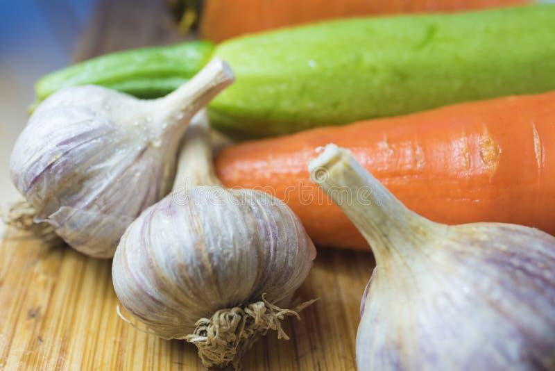 Courgette en wortelen en hoofd 3 van knoflook op een scherpe raad royalty-vrije stock afbeeldingen