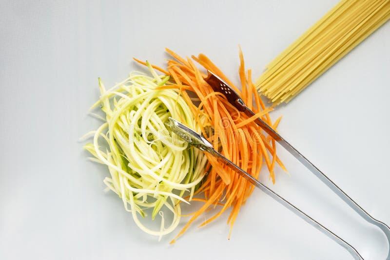 Courgette et carotte avec des spaghetti sur le hachoir blanc photo libre de droits