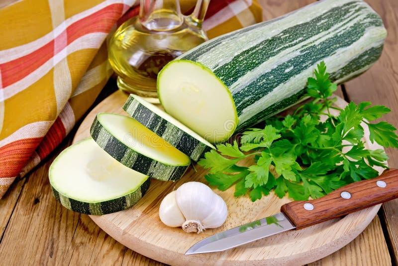 Courgette groene gestreept met olie aan boord stock afbeelding