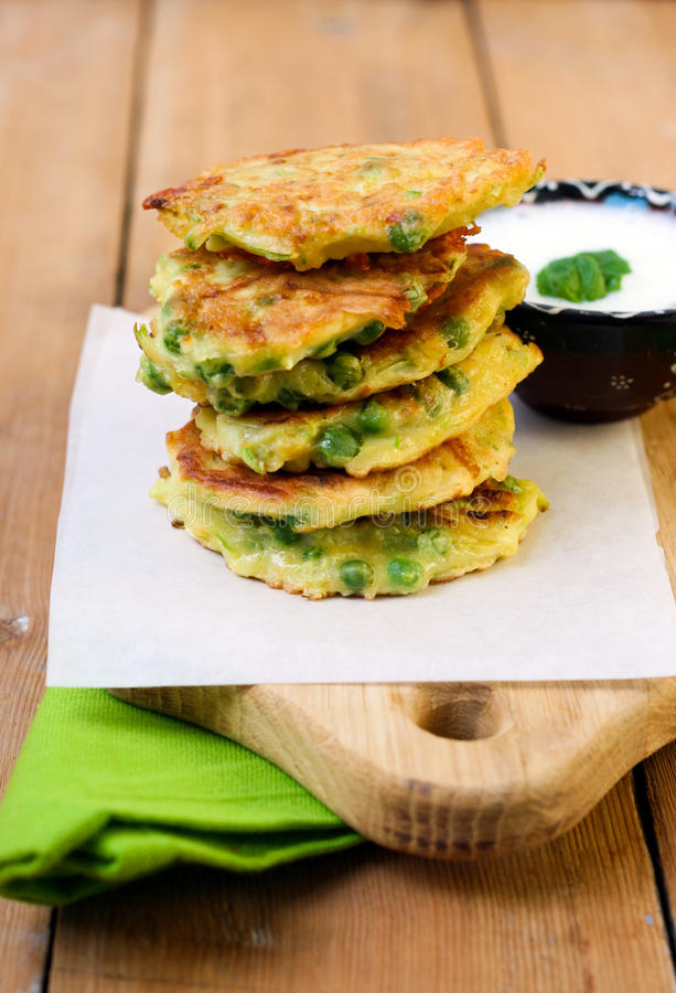 Courgette and pea patties. With yogurt stock image