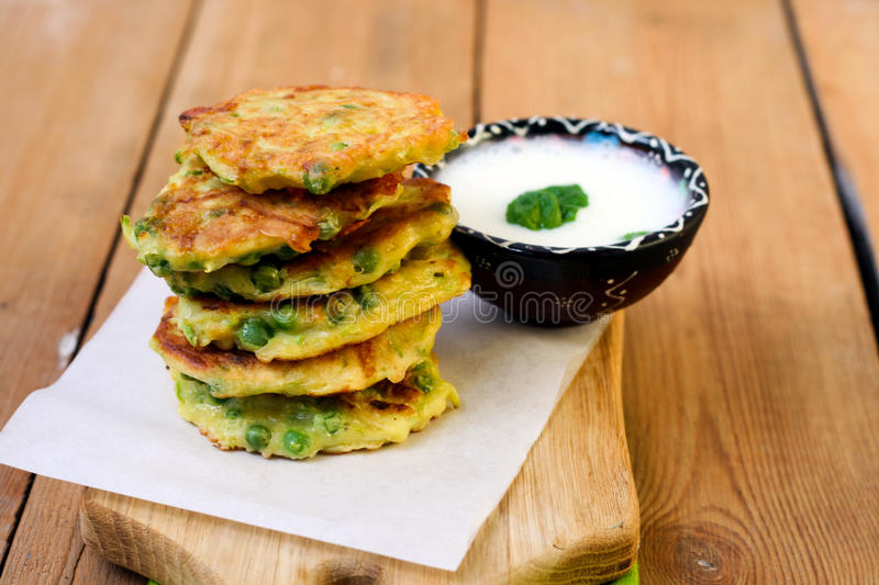 Courgette and pea patties. With yogurt stock photos