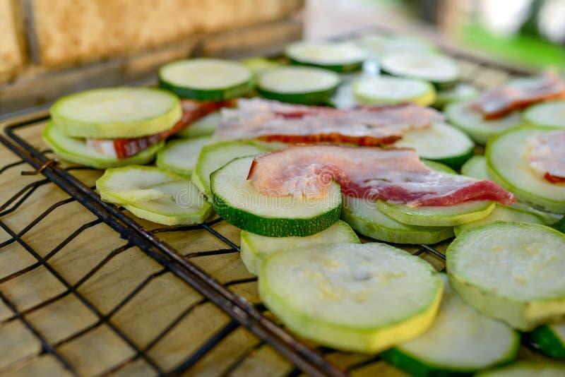 Courgette verte diététique avec des tranches de lard juteux faisant frire sur un gril au-dessus d'un feu S images libres de droits