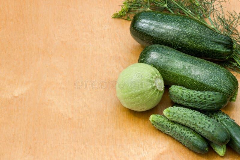 Courgettes, огурцы от кроватей сада на деревянной предпосылке Овощи страны стоковые фото