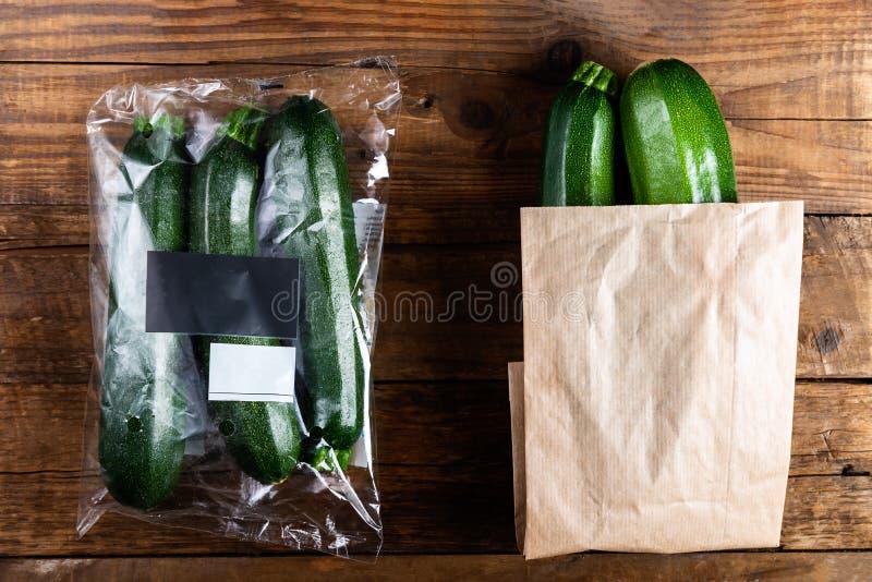 Courgettes in plastic zak VERSUS document zak Kies minder plastic concept stock foto's