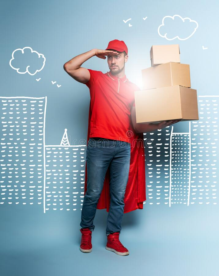 Courier acts like a powerful superhero. Concept of success and guarantee on shipment. Studio cyan background royalty free stock image