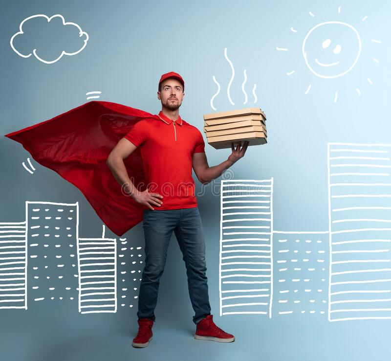 Deliveryman with pizzas acts like a powerful superhero. Concept of success and guarantee on shipment. Studio cyan royalty free stock images