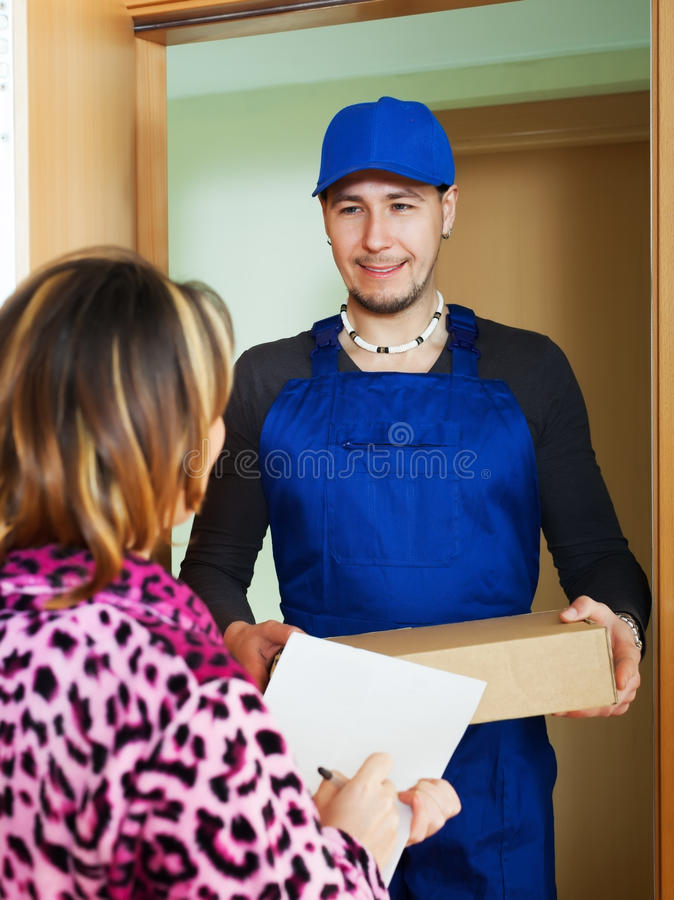 Courier brought package to girl. Courier in uniform brought package to girl at home royalty free stock photo