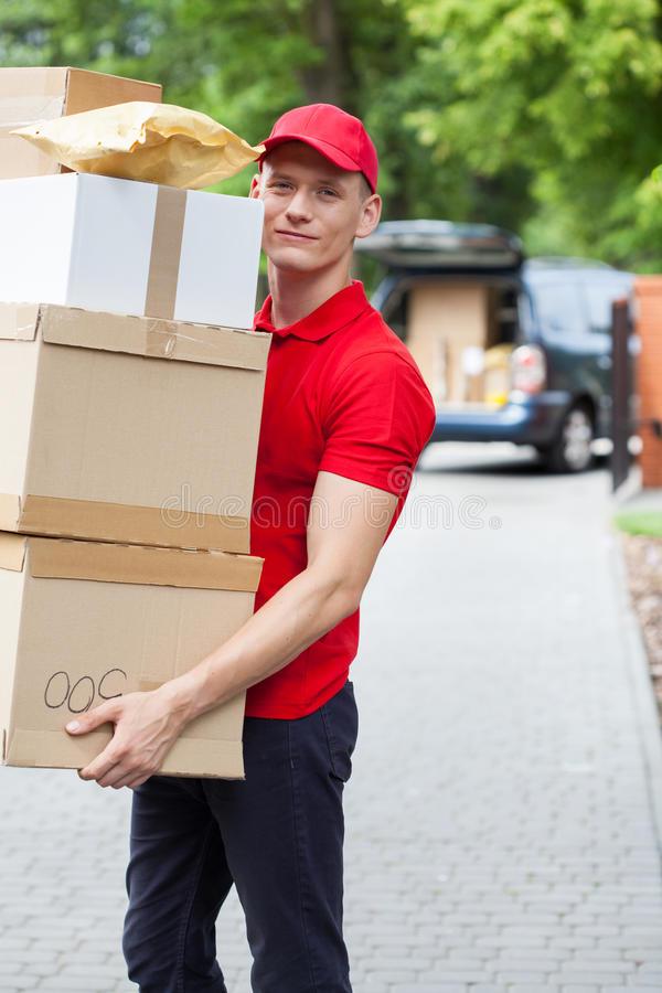 Courier with cardboard boxes. Vertical view of a courier with cardboard boxes royalty free stock photo