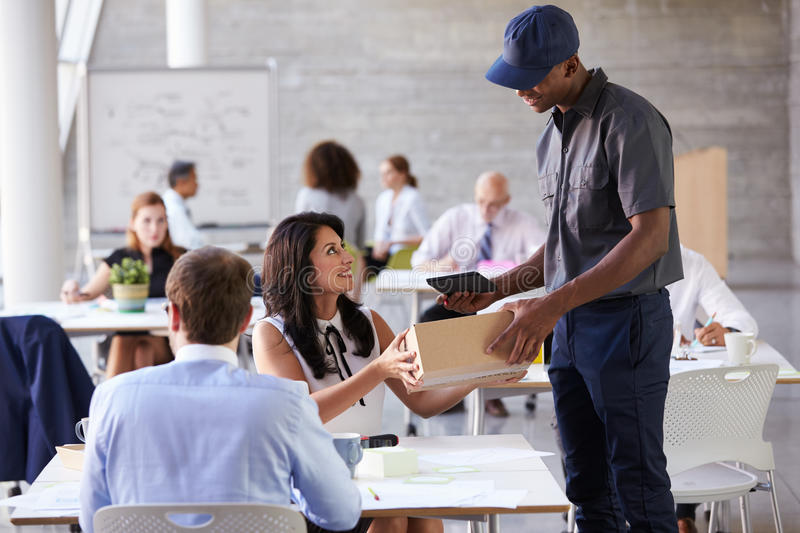 Courier Collecting Package From Businesswoman In Busy Office stock photos