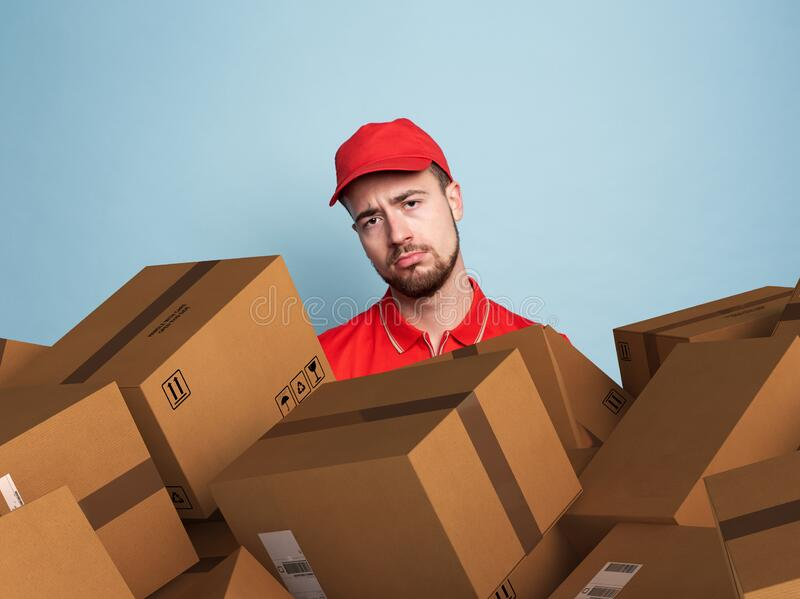 Courier is confused due to a lot of packages to deliver. concept of overwork and growth internet order. Cyan color stock image