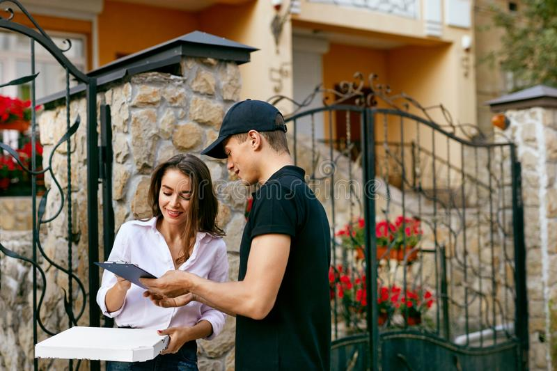 Courier Delivering Food To Client Home. Pizza Delivery royalty free stock photography