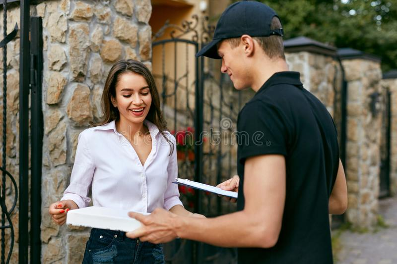 Courier Delivering Food To Client Home. Pizza Delivery royalty free stock image