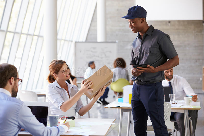 Courier Delivering Package To Businesswoman In Busy Office stock photo