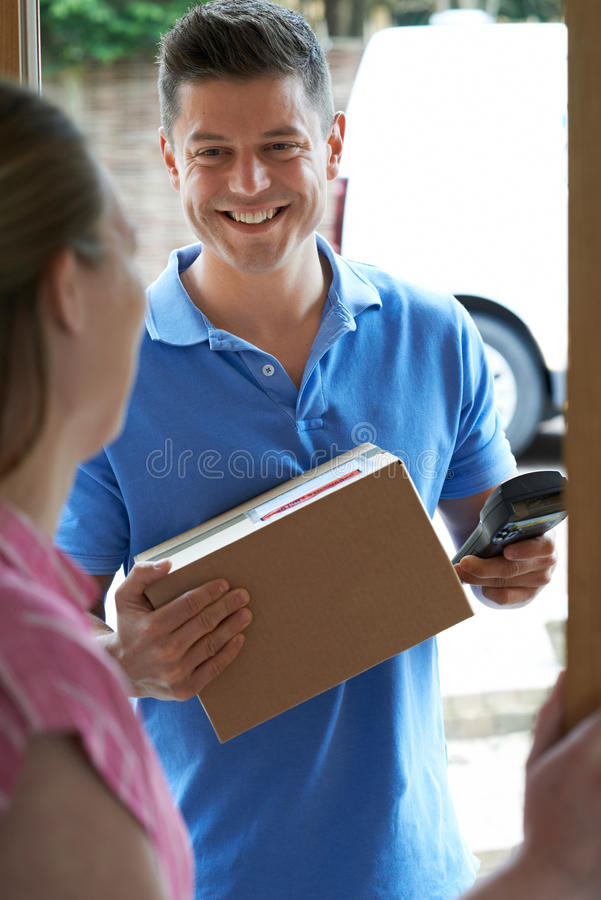 Courier Delivering Package To Domestic House. Courier Delivers Package To Domestic House stock image