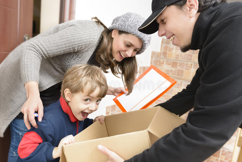 Courier Delivering a Package. To a happy boy stock image