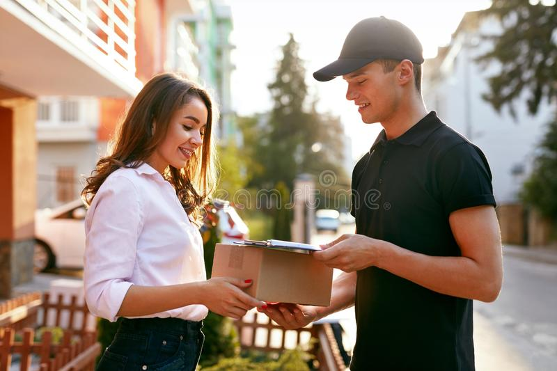 Courier Delivering Package To Woman. Client Receiving Box stock images