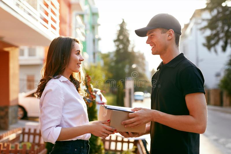 Courier Delivering Package To Woman. Client Receiving Box. From Delivery Man Near Home Outdoors. High Resolution royalty free stock images