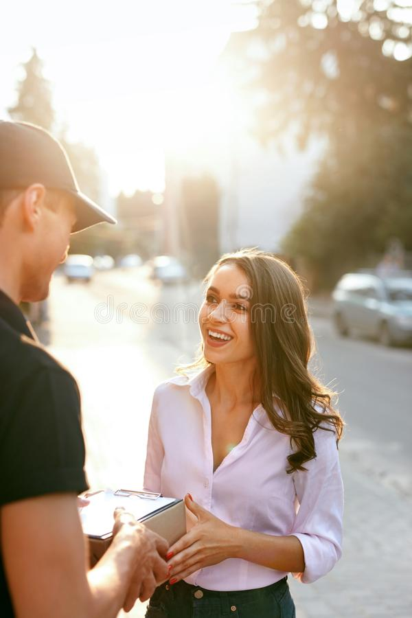 Courier Delivering Package To Woman. Client Receiving Box. From Delivery Man Near Home Outdoors. High Resolution royalty free stock photo