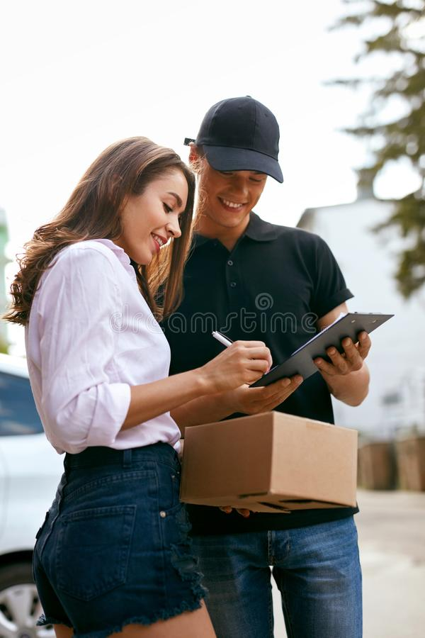 Courier Delivering Package To Woman At Home. Female Receiving Box From Delivery Man Outdoors. High Resolution stock images