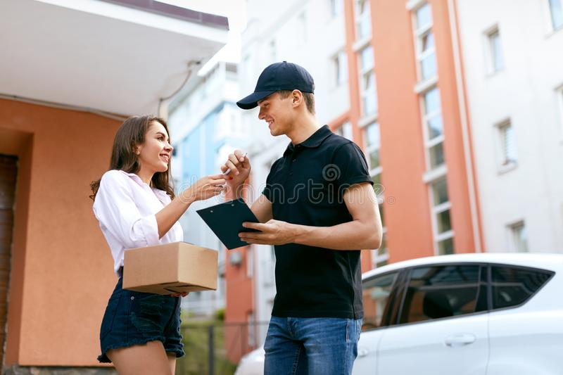 Courier Delivering Package To Woman At Home. Female Receiving Box From Delivery Man Outdoors. High Resolution stock photo