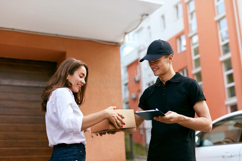 Courier Delivering Package To Woman At Home. Female Receiving Box From Delivery Man Outdoors. High Resolution stock photos