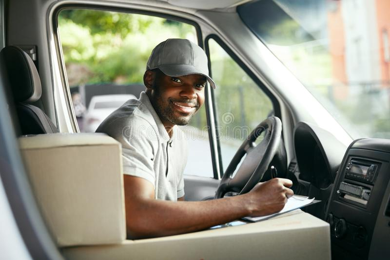 Courier Delivery. Black Man Driver Driving Delivery Car. With Boxes And Packages. High Resolution royalty free stock photos