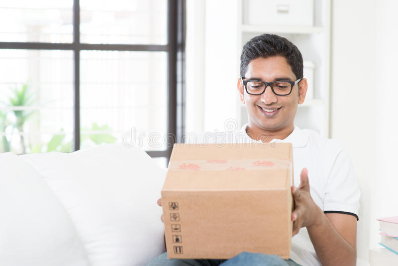 Courier delivery concept. Indian guy received an express parcel and checking the box at home. Asian man sitting on sofa indoor. Handsome male portrait royalty free stock photo