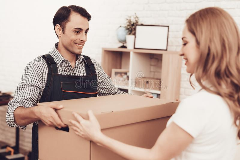 Courier in Blue Clothes Gives Woman Paper Box. Courier Delivery. Man with Brown Box. White Interior. Deliveryman Arab Nationality. Courier in Blue Clothes stock images