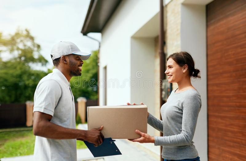 Courier Delivery. Man Delivering Package To Woman At Home stock photo