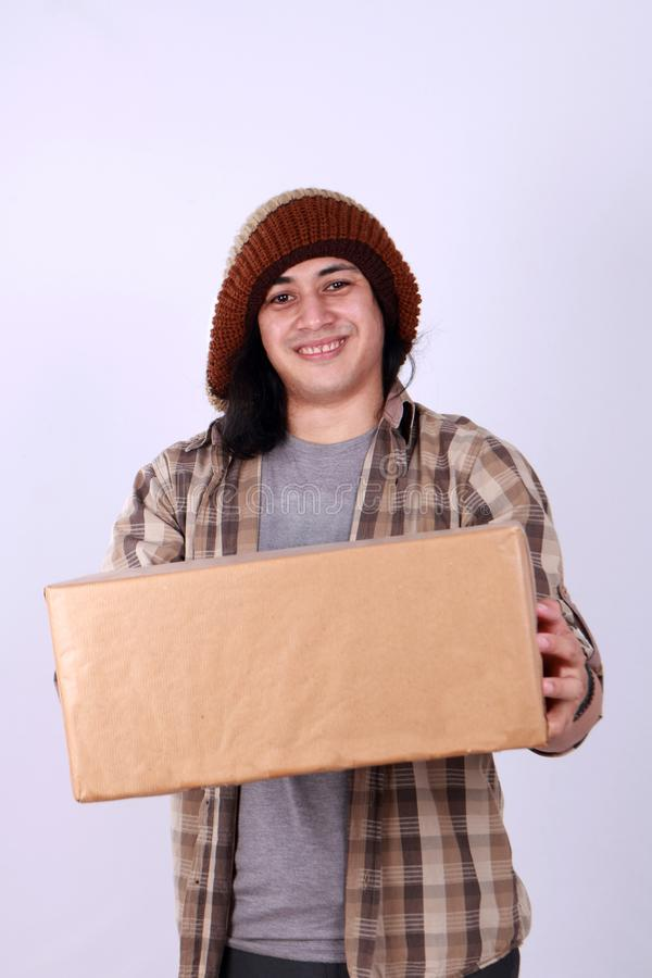 Courier Delivery Man Giving Box. Portrait of young good looking Asian courier delivery man giving box of parcel package, looking at camera amd smiling, isolated royalty free stock photos